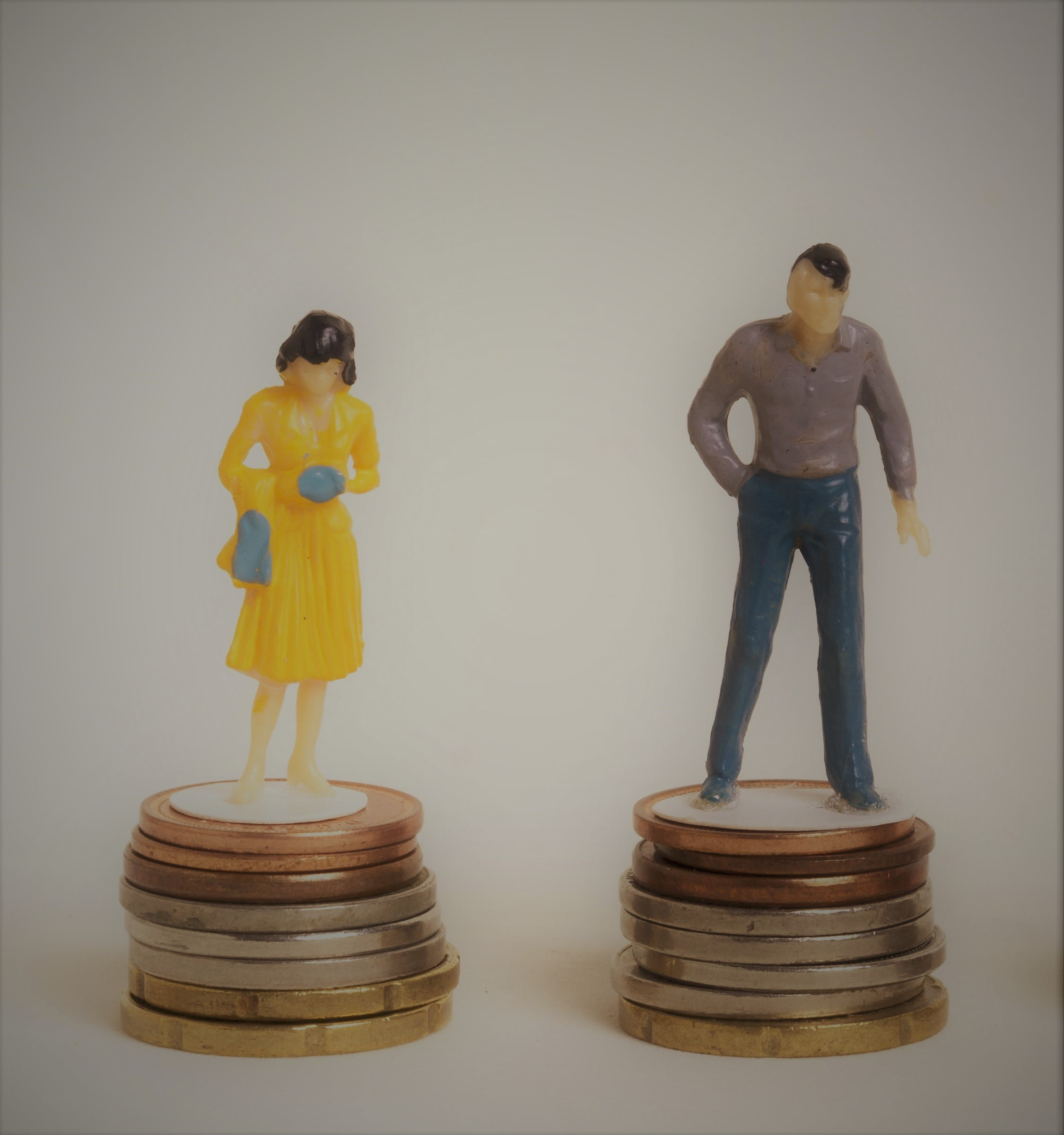 business-man-and-woman-sitting-on-equal-piles-of-coins-min.jpg