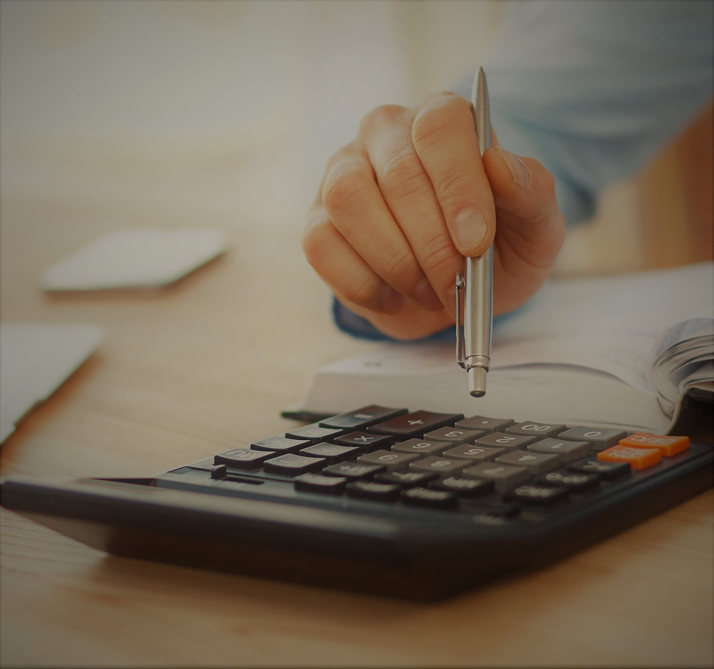 close-up-detail-of-professional-serious-accountant-sitting-in-light-office-checking-company-finance-profits-on-calculator-1.jpg
