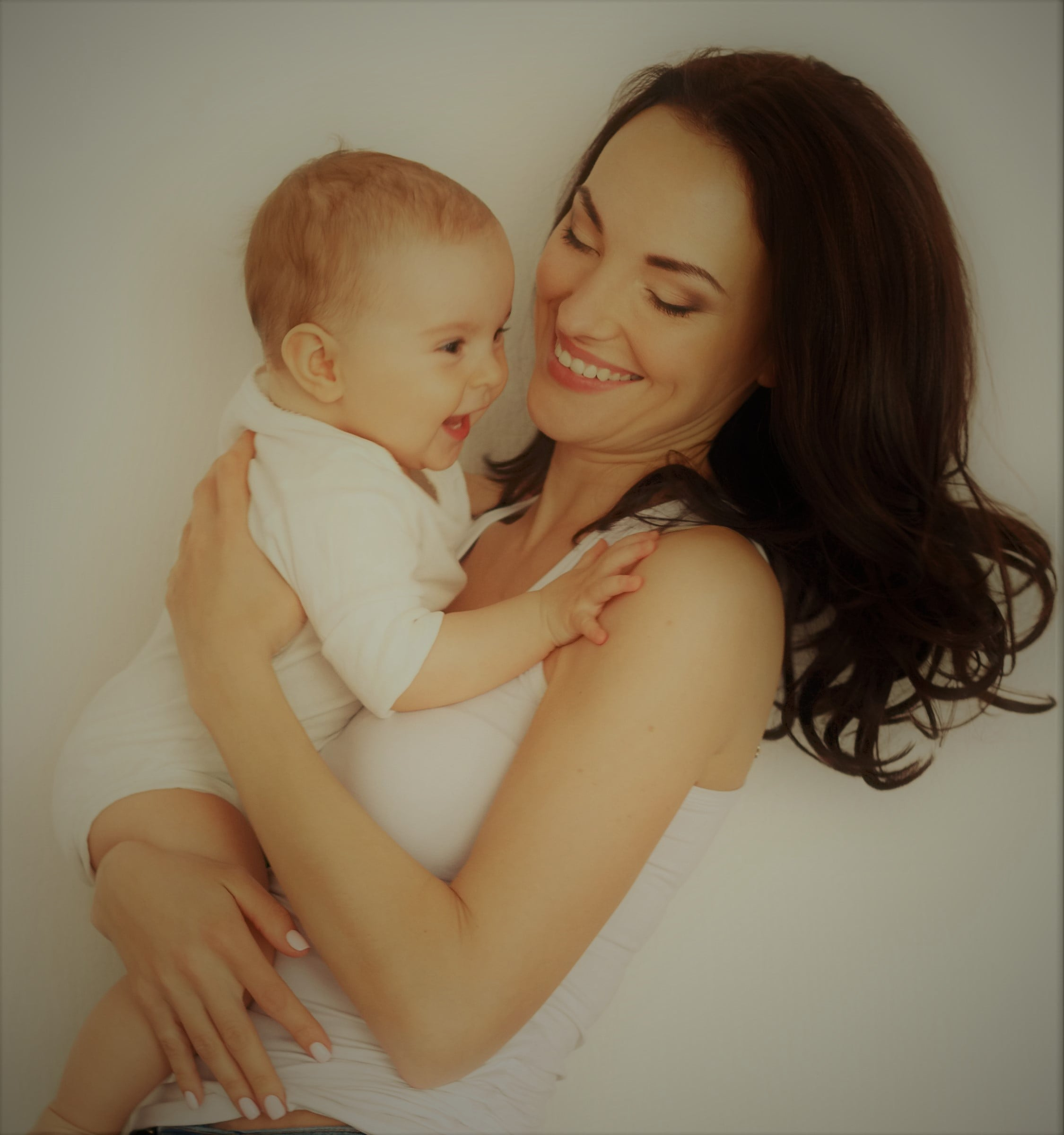 young-happy-mother-smiling-holding-looking-her-baby-daughter-white-wall-min.jpg